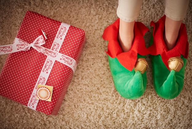 Pernas de elf ao lado do presente de natal