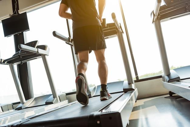 Pernas de esportista correndo na esteira no centro de fitness ginásio. esporte e conceito de estilo de vida saudável.