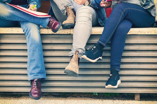 Pernas de estudantes sentados em um banco.