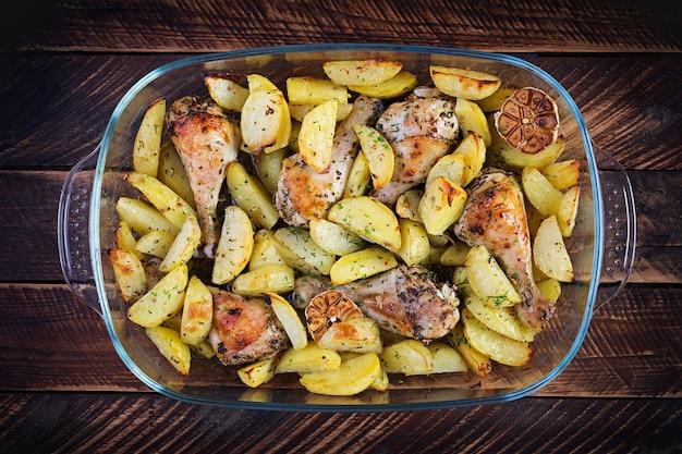Pernas de frango assado com batatas fatiadas e ervas. coxinhas de frango no churrasco. vista superior, sobrecarga, copie o espaço.