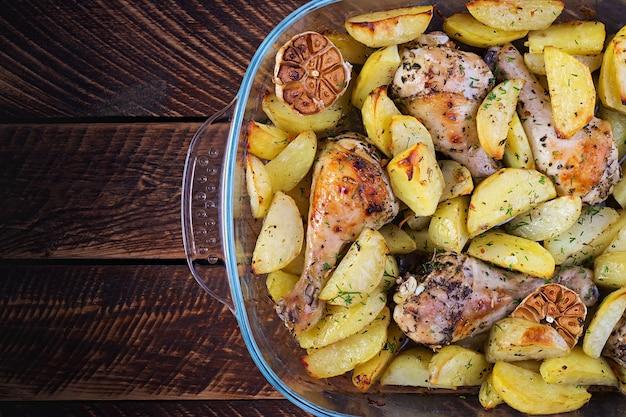 Pernas de frango assado com batatas fatiadas e ervas.