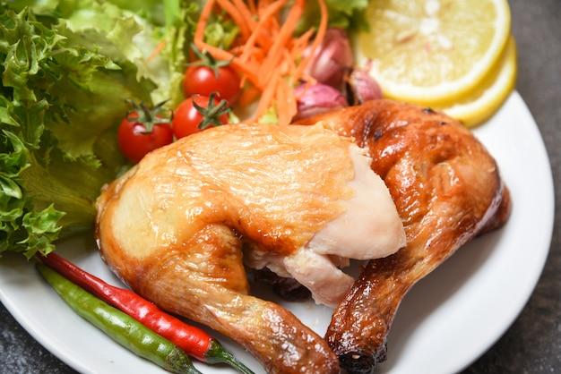 Pernas de frango assado na chapa branca com pimenta limão especiarias especiarias ervas e salada de alface vegetal