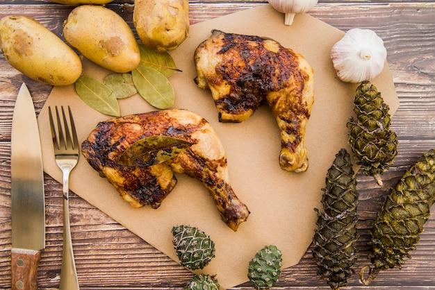 Pernas de frango assado na mesa de madeira