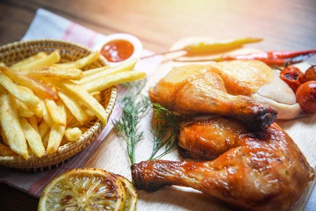 Pernas de frango assado na tábua de madeira e batatas fritas cesta com pimenta de limão de milho especiarias ervas picantes