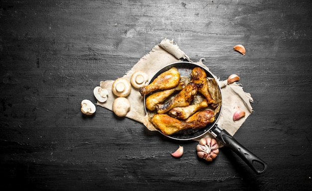 Pernas de frango com cogumelos e alho em um fundo preto de madeira