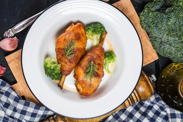 Pernas de frango com legumes na mesa de madeira.