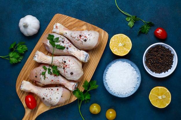 Pernas de frango com temperos e sal, pronto para cozinhar na tábua.