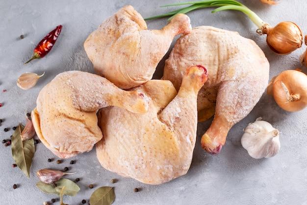 Pernas de frango congeladas sobre um fundo claro de concreto. carne de frango crua. vista superior, copie o espaço