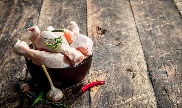 Pernas de frango cru com alho e especiarias em uma tigela na mesa de madeira.