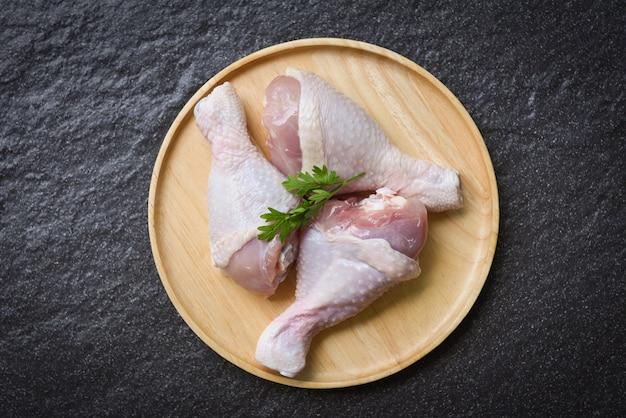 Pernas de frango cru com ervas na placa de madeira