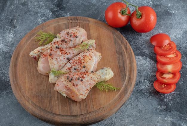 Pernas de frango cru com especiarias e tomates fatiados ou inteiros em uma placa de madeira.