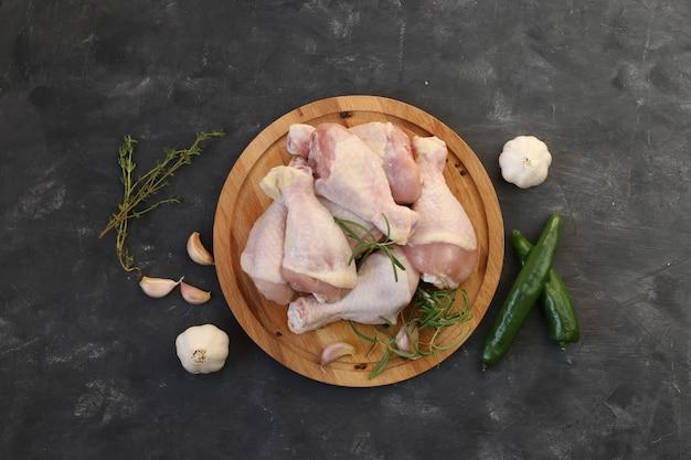 Pernas de frango cru com especiarias em uma placa em um fundo preto. vista do topo.