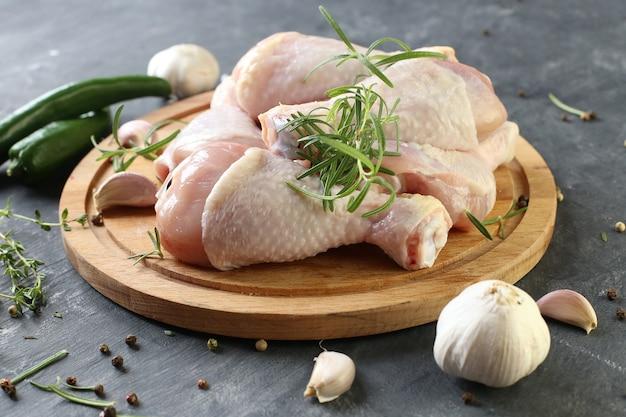 Pernas de frango cru com especiarias em uma placa em um fundo preto.