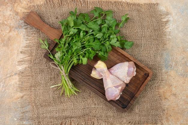 Pernas de frango cru com verduras na tábua de madeira no saco.