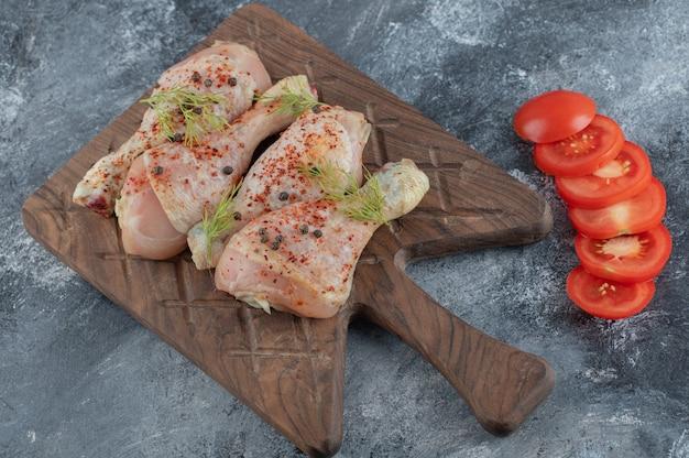 Pernas de frango cru e fatias de tomate orgânico na mesa da cozinha.