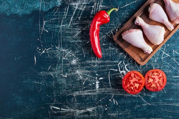 Pernas de frango cru em uma placa de madeira.