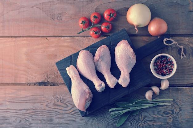 Pernas de frango cru em uma tábua de madeira, cebola, alho, temperos e um raminho de alecrim
