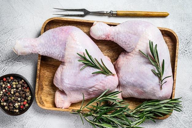 Pernas de frango cru em uma tábua