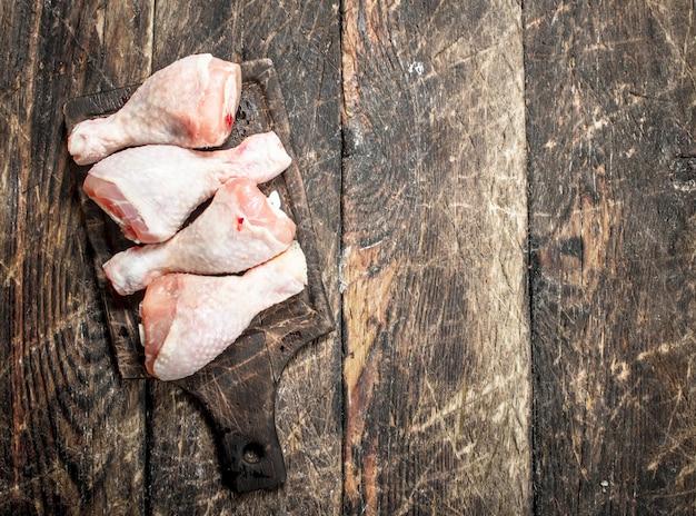 Pernas de frango cru na placa de corte na mesa de madeira.
