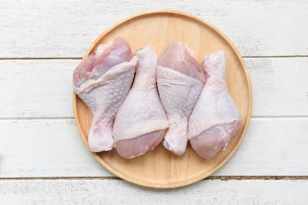 Pernas de frango cru na placa de madeira / carne de frango cru fresco para cozinhar