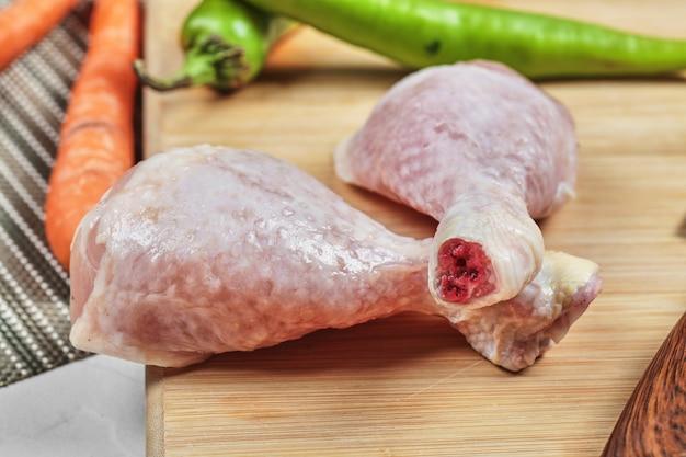 Pernas de frango cru na placa de madeira com pimenta