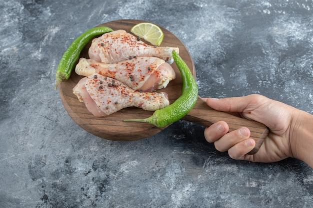 Pernas de frango cru na tábua de madeira na mão do homem.