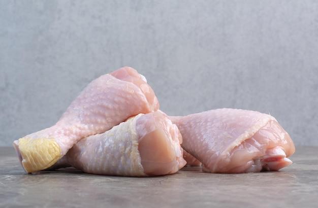 Pernas de frango cru no fundo de mármore. foto de alta qualidade
