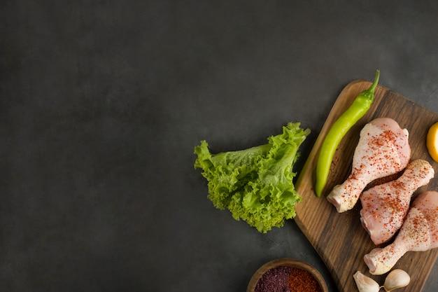Pernas de frango cru servidas com verdura