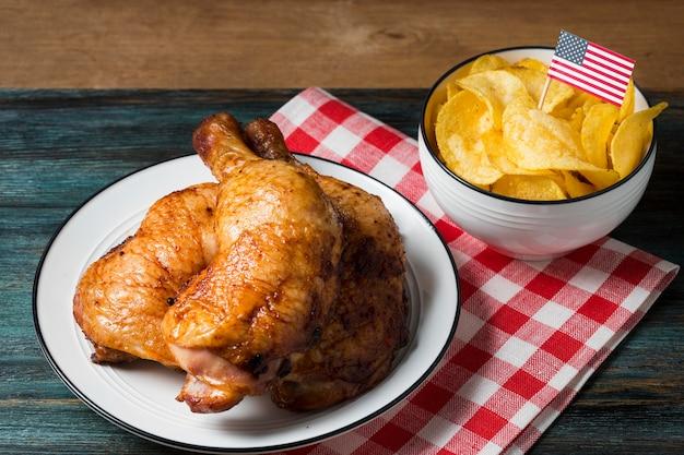 Pernas de frango de ângulo alto no prato com batatas fritas