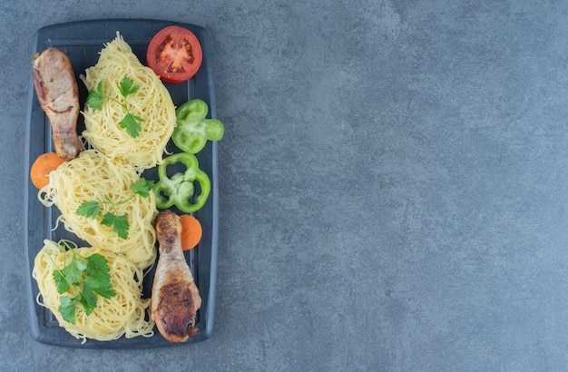 Pernas de frango e espaguete na placa de madeira.