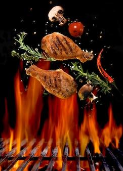 Pernas de frango e ingredientes picantes voando sobre uma churrasqueira vermelha