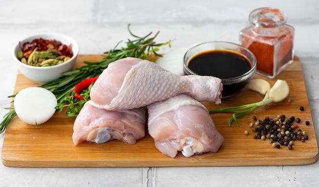 Pernas de frango em uma tábua com especiarias e temperos