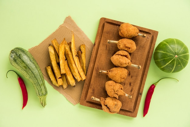 Pernas de frango fast-food e batatas fritas, organizando com legumes sazonais