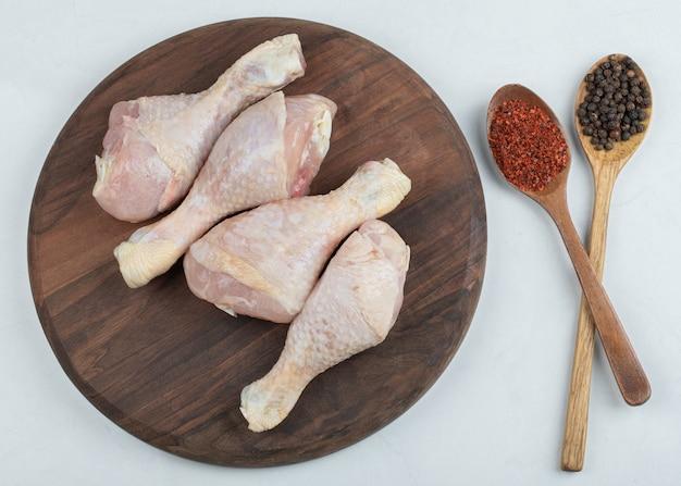 Pernas de frango fresco cru com duas colheres de pimentão no fundo branco.