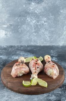 Pernas de frango fresco marinado e fatias de limão na placa de madeira.