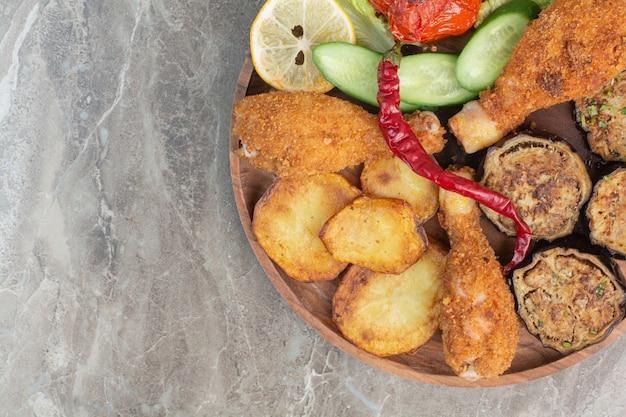 Pernas de frango frito com batata e berinjela na placa de madeira.