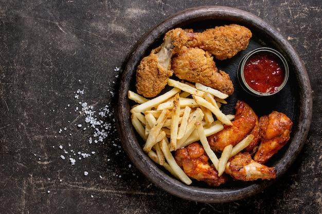 Pernas de frango frito com batata frita