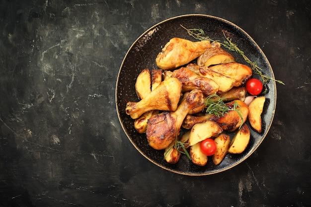 Pernas de frango frito com especiarias e batatas fritas em um prato sobre um fundo preto