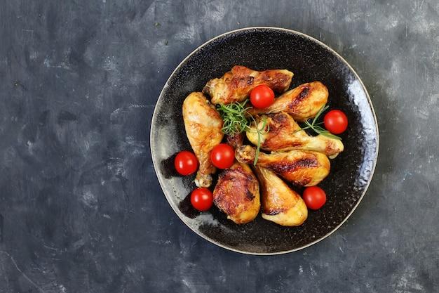 Pernas de frango frito com especiarias em um prato em uma vista superior de fundo preto.