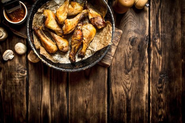 Pernas de frango frito com molho de tomate. em uma mesa de madeira.