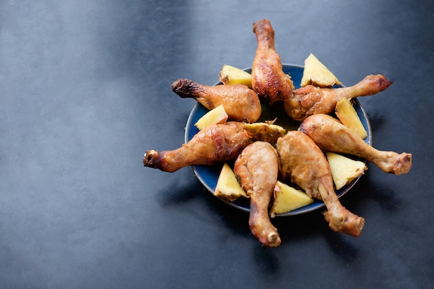 Pernas de frango frito com pedaços de abacaxi no prato azul na superfície da mesa preta