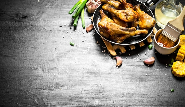 Pernas de frango frito com pedaços de milho e molho de tomate