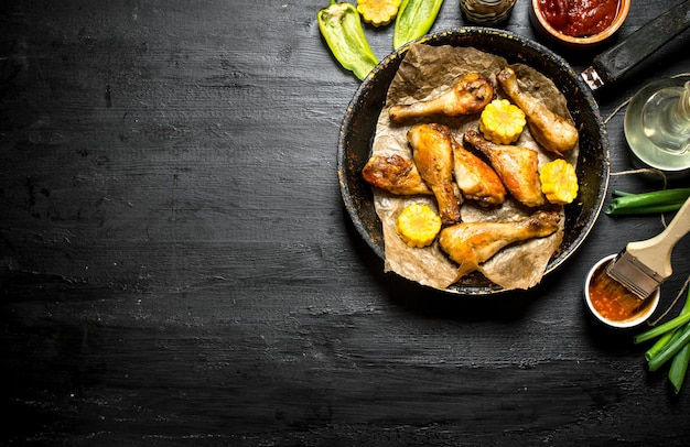 Pernas de frango frito com pedaços de milho e molho de tomate.