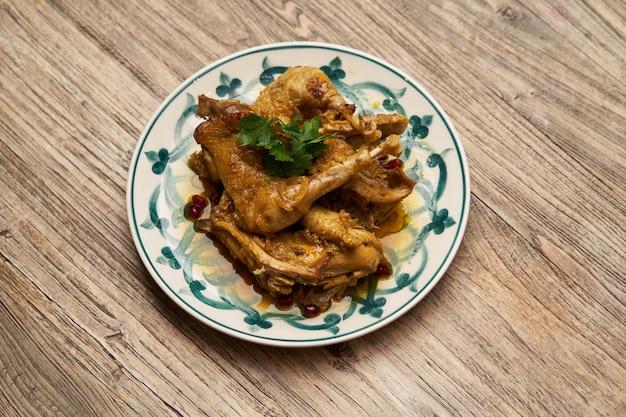 Pernas de frango frito com romã e salsa no fundo da mesa de madeira com espaço de cópia, vista superior