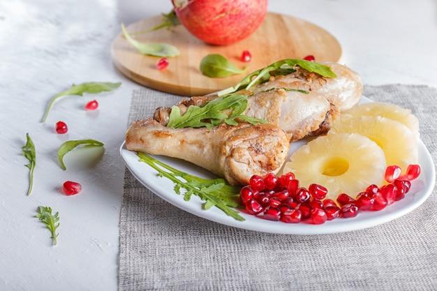 Pernas de frango frito com sementes de abacaxi e romã rúcula em fundo branco de madeira
