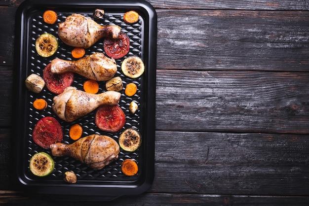 Pernas de frango frito com vegetais e ervas, comida deliciosa e aperitivo, lugar para texto