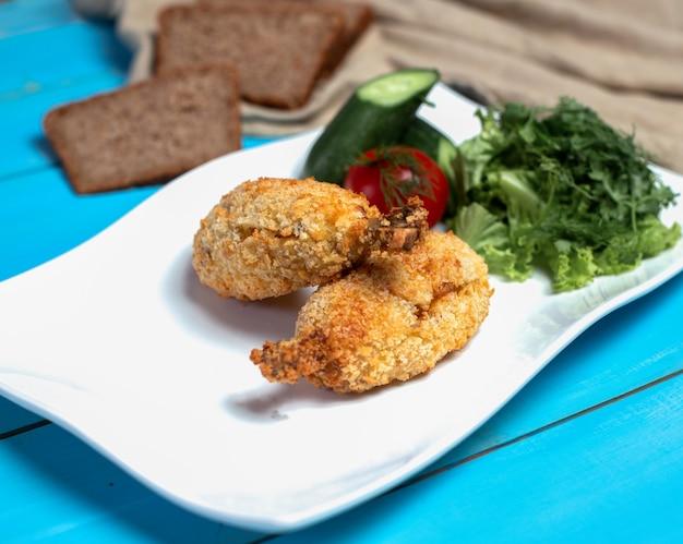Pernas de frango frito crocantes com salada verde.