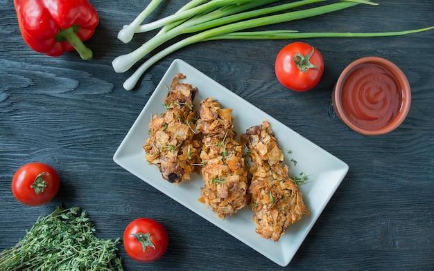 Pernas de frango frito crocantes empanadas com batatas fritas. baquetas assadas são decoradas com legumes e ervas. comida rápida. comida errada. fundo de madeira escuro.