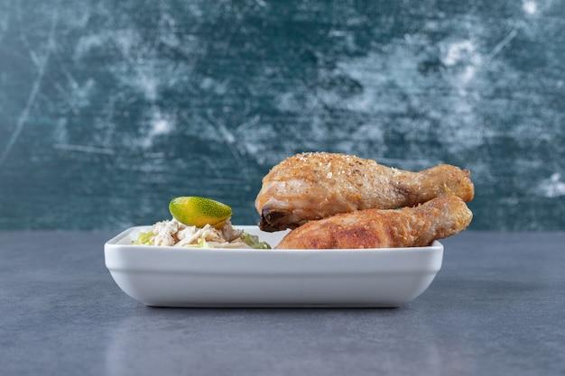 Pernas de frango frito e salada na chapa branca.