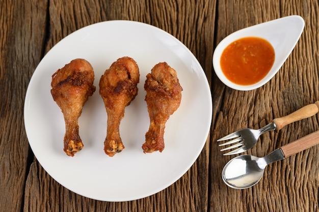 Pernas de frango frito em um prato branco com colher, garfo e molho.